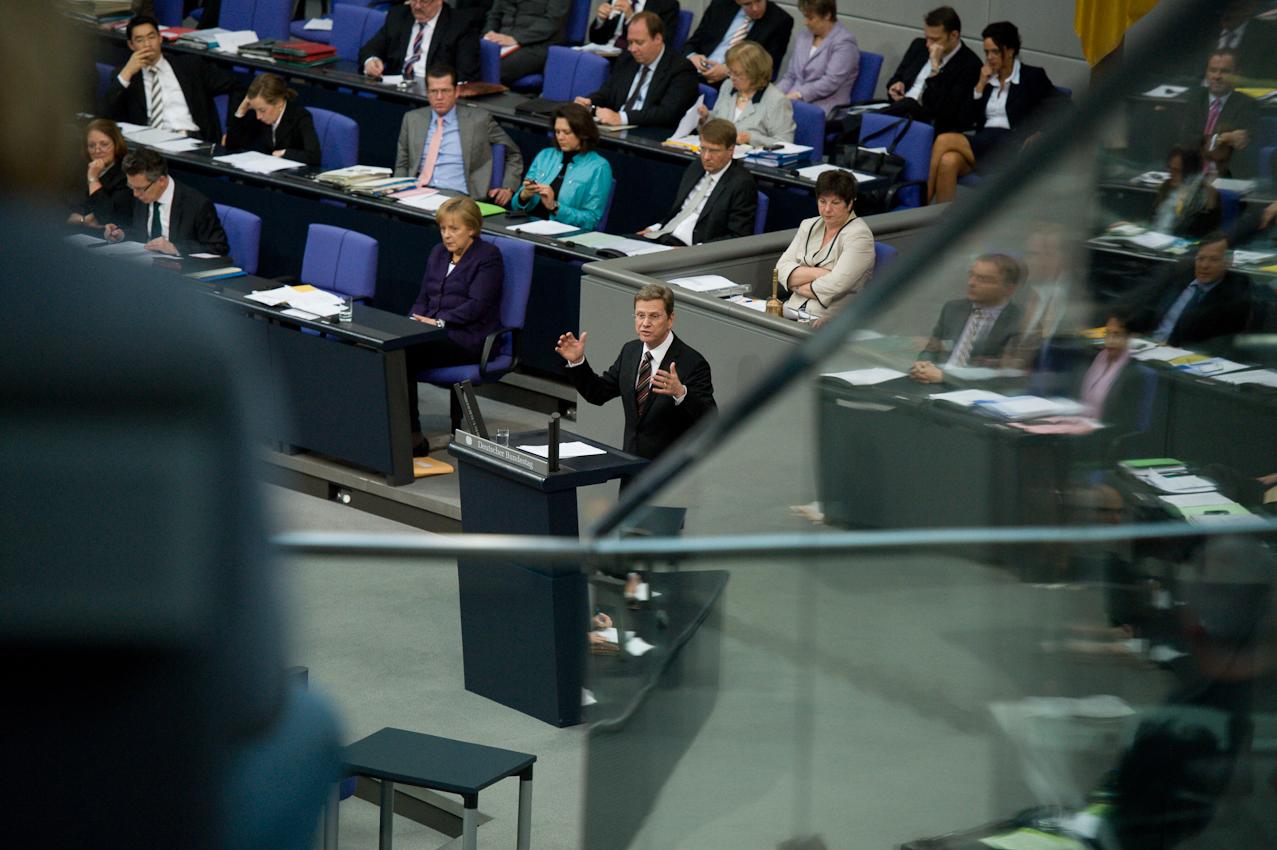 """07 MAI 2010, BERLIN/GERMANY: Bundesaußenminister Guido Westerwelle (M) (FDP), halt eine Rede wahrend der Bundestagsdebatte zur sog. Griechenlandhilfe, laut Tagesordnung """"Übernahme von Gewährleistungen zum Erhalt der für die Finanzstabilität in der Wahrungsunion erforderlichen Zahlungsfähigkeit der Hellenischen Republik (Währungsunion-Finanzstabilitätsgesetz - WFStG)"""", links Angela Merkel und Teile der Bundesregierung in der Regierungsbank, Plenum, Deutscher Bundestag"""