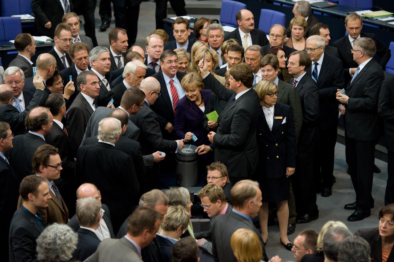 """07 MAY 2010, BERLIN/GERMANY: Bundeskanzlerin Angela Merkel (M) (CDU) wahrend der Stimmabgabe bei der namentlichen Abstimmung, nach der Bundestagsdebatte zur sog. Griechenlandhilfe, laut Tagesordnung """"Übernahme von Gewährleistungen zum Erhalt der für die Finanzstabilität in der Wahrungsunion erforderlichen Zahlungsfähigkeit der Hellenischen Republik (Währungsunion-Finanzstabilitätsgesetz - WFStG)"""", Plenum, Deutscher Bundestag"""