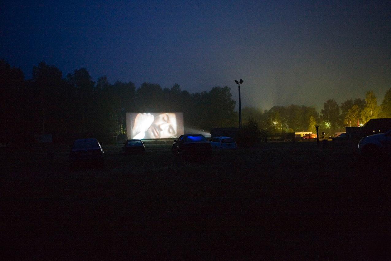 Trotz regnerischem Wetters sind einige Kinobesucher zur Vorstellung von Sherlock Holmes gekommen. Sieben Autos haben ihren Platz auf dem Hang des Kinogelaendes in Zempow eingenommen. Die Scheiben beschlagen in regelmaessigen Abstaenden. Im Hintergrund erleuchten die Laternen der Kinozufahrt den naechtlichen Himmel.