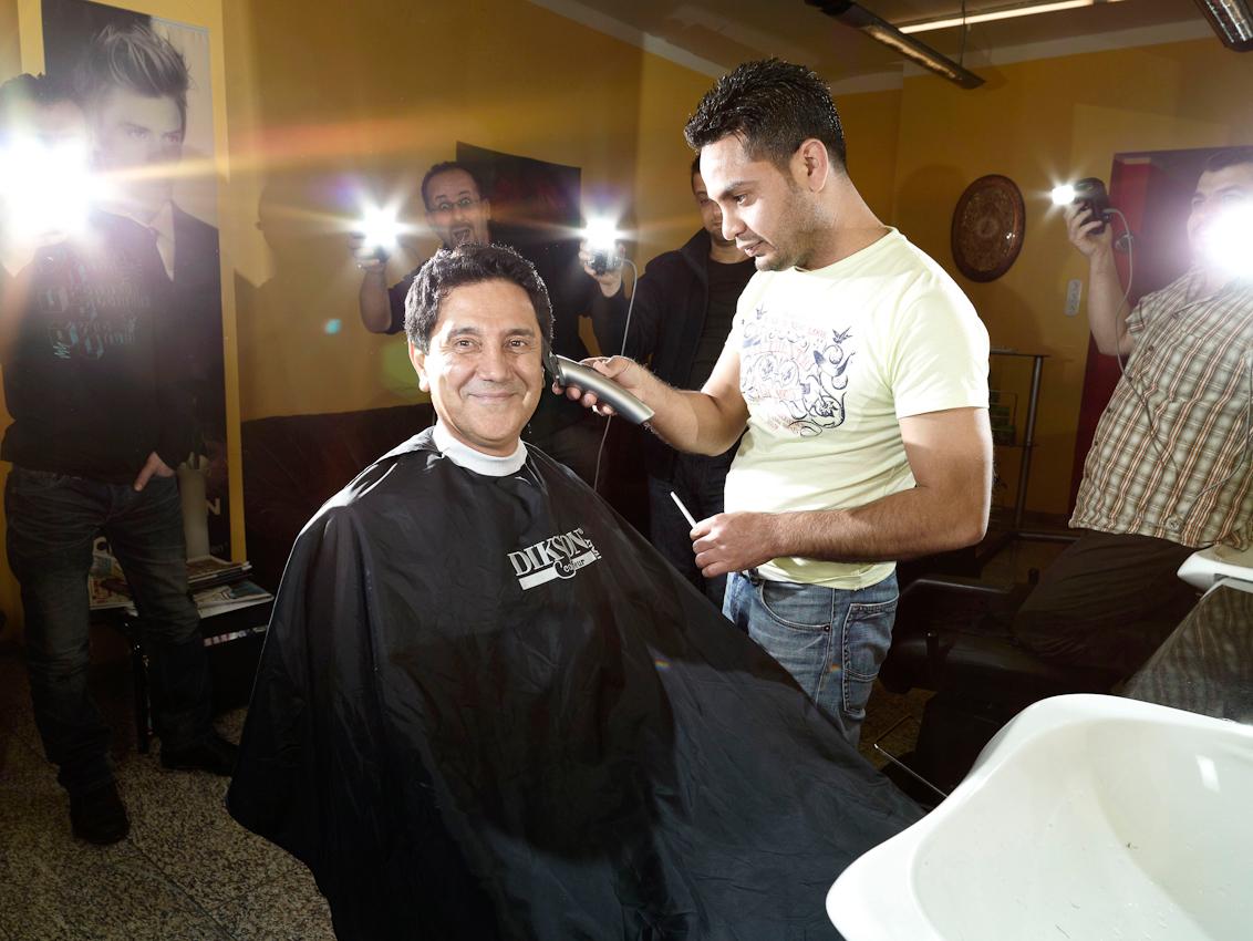 Behzad Maighami lässt sich die Haare von Ahmad Mahmud Ahmad schneiden.