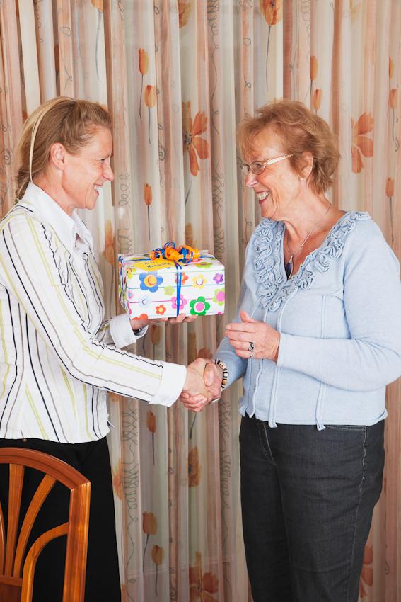 """In Eitorf wurde am 7. Mai 2010 der katholische Namenstag """"Gisela"""" bei Kaffee und Kuchen traditionsgemäß mit Freunden und Familie gefeiert. Die Fotografin Gaby Wojciech (links) gratuliert Ihrer Mutter Gisela Wojciech (rechts) zum Namenstag und überreicht ein Namenstagsgeschenk. Es wurde im privaten Esszimmer und Wohnhaus von Gisela Wojciech gefeiert. Dr. Axel Knicker hat für diese Aufnahme der Fotografin assistiert. Das Bild wurde um 15.41 Uhr zur klassischen deutschen Kaffee und Kuchenzeit aufgenommen."""