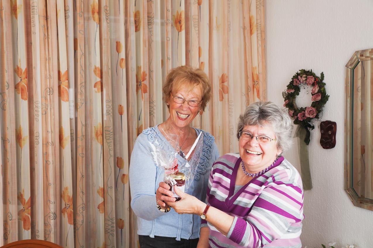 Die Kartenspiel- und Nordic Walking-Freundin Inge Wagner (rechts) gratuliert Gisela Wojciech (links) zum Namenstag und überreicht eine selbstgemachte Marmelade als Namenstagsgeschenk.