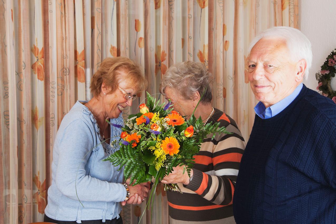 Margret Derscheid (Mitte) und ihr Mann Otto Derscheid (rechts) gratulieren Ihrer gemeinsamen sehr guten Freundin Gisela Wojciech (links). Margret Derscheid Überreicht einen Blumenstrauß und spricht leise sehr persönliche Wünsche hinter dem Blumenversteck aus. Otto Derscheid wartet den Plausch der beiden langjährigen Freundinnen geduldig ab, um dann selbst auch zu gratulieren.