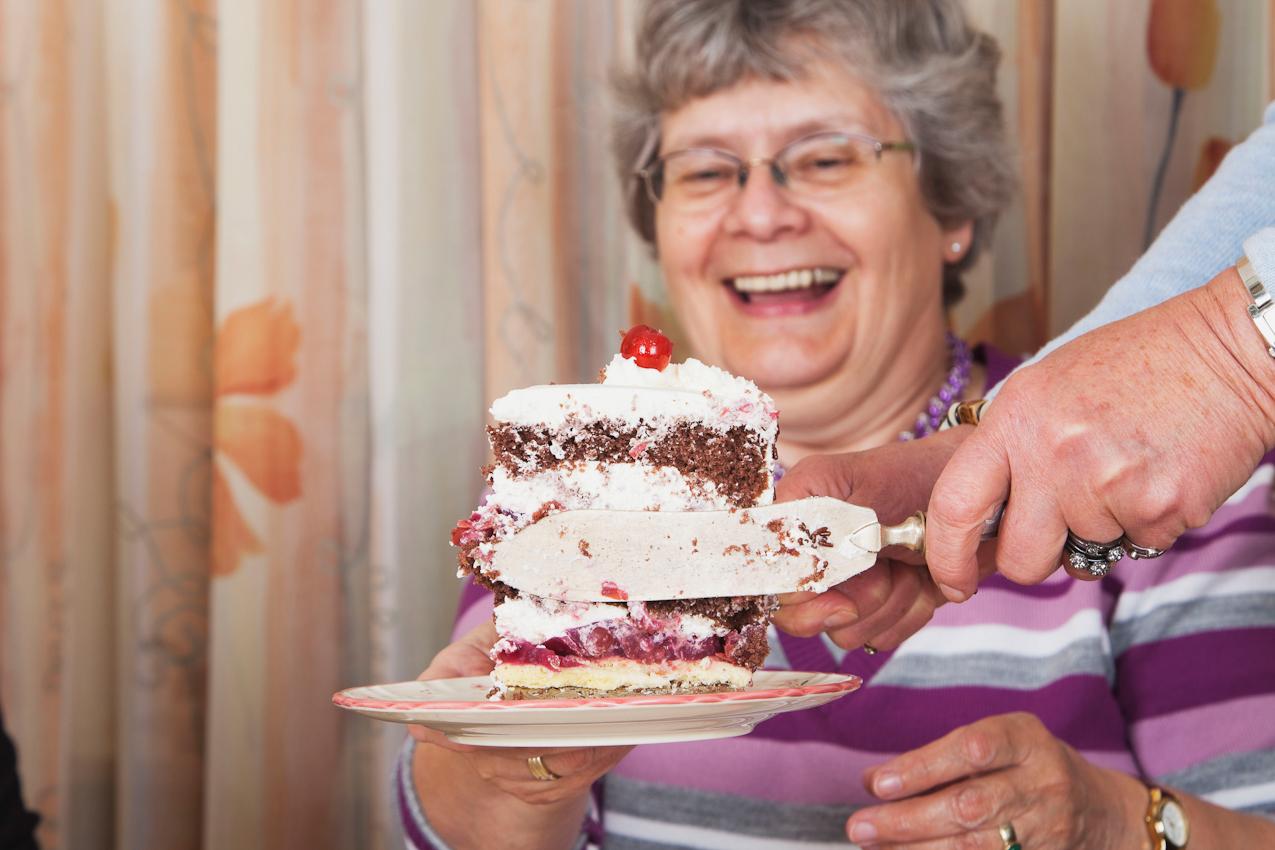"""Gisela Wojciech (nur die Hände am Kuchenmesser im Bild) hat die Schwarzwälderkirsch-Namenstagstorte angeschnitten und balanciert ein Kuchenstück auf den Kuchenteller ihrer Freundin Inge Wagner (im Hintergrund). Inge freut sich schon riesig auf ihr """"kleines Kuchenstückchen""""."""