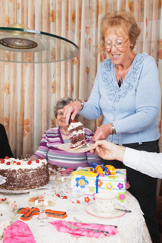 """Gisela Wojciech hat die Schwarzwälderkirsch-Namenstagstorte angeschnitten und balanciert ein """"kleines Kuchenstückchen"""" auf den Kuchenteller des Schwiegersohnes (Arm rechts im Bild). Im Hintergrund erfreut sich die Freundin Inge Wagner an dem Kuchenmanöver. Auf dem Tisch liegen ein Namenstagsgeschenk und ein Keramik-Kruzifix."""