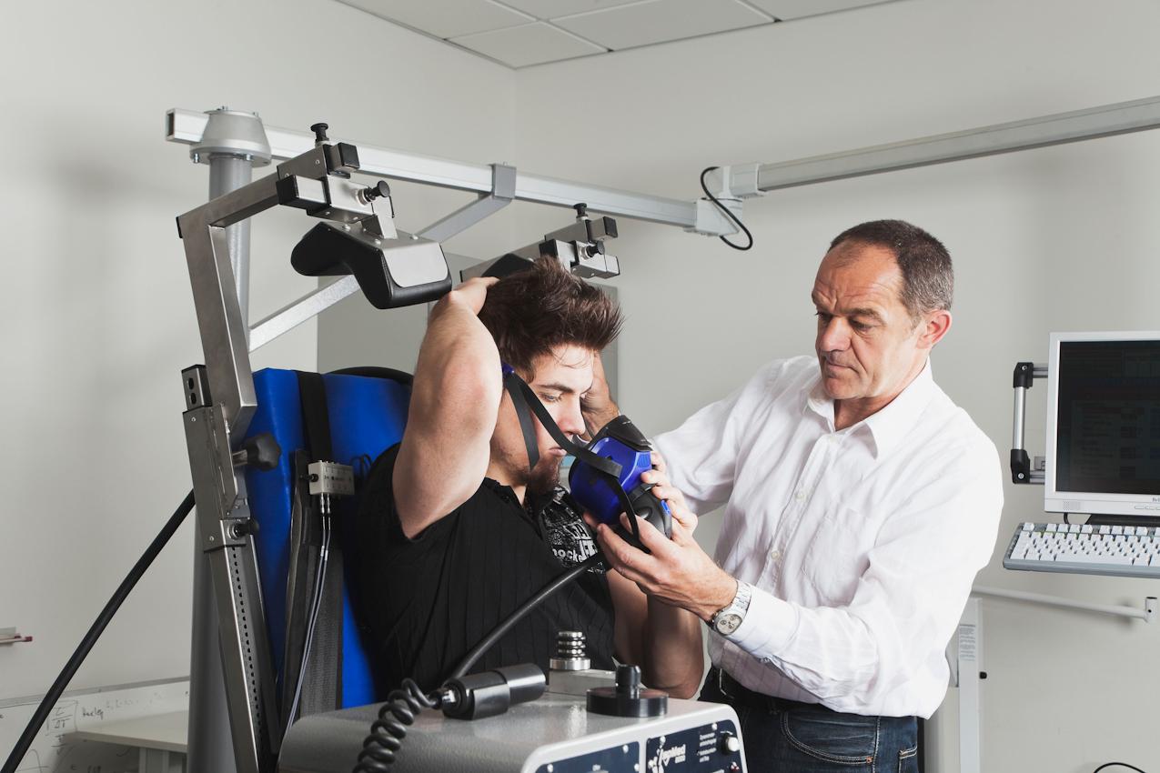 An der Deutschen Sporthochschule Köln werden im Institut für Bewegungs- und Neurowissenschaften die Muskel- und Gehirnaktivitäten unter Sauerstoffmangel bei Krafttraining erforscht. Der Proband Fabian Schurg (links) sitzt auf einer elektronisch gesteuerten Kraftmaschine. Der Laborleiter Dr. Axel Knicker (rechts im Bild) passt dem Proband die Atemmaske an, die ihn während des Experimentes mit der sauerstoffreduzierten Atemluft versorgen soll.