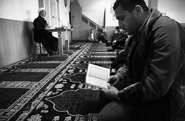 Ein Mann liest in einem arabischen Koran, während der Imam seine Predigt auf Türkisch hält