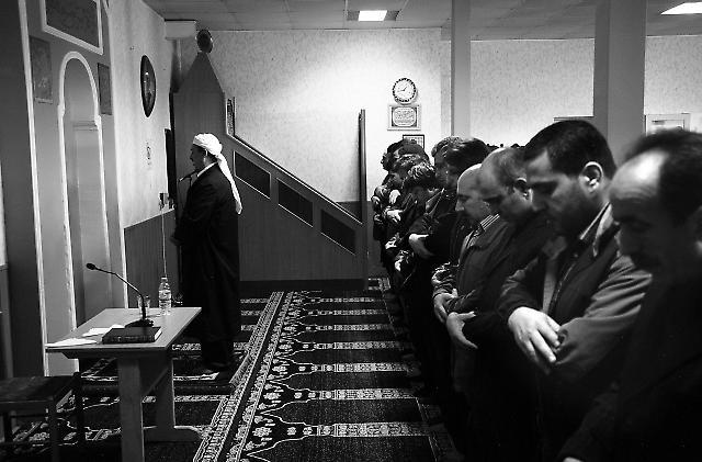 Männer vollziehen das Freitagsgebet hinter dem Imam