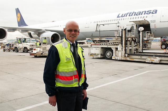 Ein Lufthansa Operations Officer posiert vor einer Passagiermaschine vom Typ Airbus A 340-600 am Terminal 2, deren Beladung er beaufsichtigt. Der Frankfurter Flughafen ist die größte Arbeitsstätte Deutschlands.